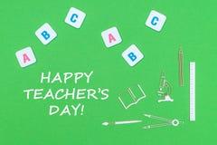 Smsa den lyckliga dagen för lärare` s, från ovannämnda träminituresskolatillförsel och abc-bokstäver på grön bakgrund Arkivfoto