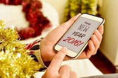 Smsa det lyckliga nya året 2016 i smartphonen av en man Royaltyfri Foto