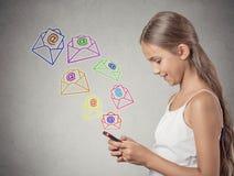 Smsa för smartphone för flicka som hållande överför meddelandet Arkivfoton