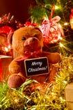 Smsa glad jul, nallebjörnen och gåvor under en jultre Arkivfoton