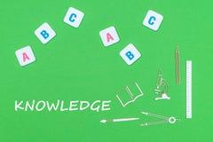 Smsa knowlwdge, från ovannämnda träminituresskolatillförsel och abc-bokstäver på grön bakgrund Arkivfoton