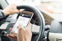 Smsa, medan köra bilen Ansvarslös man som överför sms arkivfoton