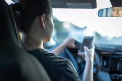 Smsa och körning Kvinna som använder telefonen bak hjulet royaltyfri bild
