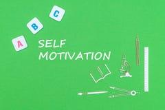 Smsa självmotivationen, från ovannämnda träminituresskolatillförsel och abc-bokstäver på grön bakgrund Arkivbilder