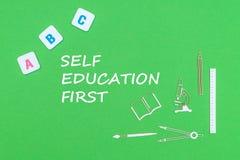 Smsa självutbildning först, från ovannämnda träminituresskolatillförsel och abc-bokstäver på grön bakgrund Royaltyfria Foton