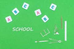 Smsa skolan, från ovannämnda träminituresskolatillförsel och abc-bokstäver på grön bakgrund royaltyfri bild