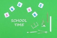 Smsa skolatid, från ovannämnda träminituresskolatillförsel och abc-bokstäver på grön bakgrund Arkivbild