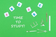 Smsa tid att studera, från ovannämnda träminituresskolatillförsel och abc-bokstäver på grön bakgrund Arkivfoto