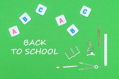 Smsa tillbaka till skolan, från ovannämnda träminituresskolatillförsel och abc-bokstäver på grön bakgrund Arkivbilder
