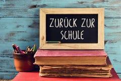 Smsa tillbaka till skolan i tysk i en svart tavla Royaltyfri Foto