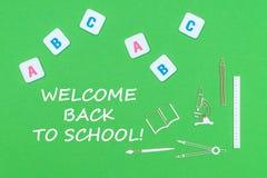 Smsa välkomnandet tillbaka till skolan, från ovannämnda träminituresskolatillförsel och abc-bokstäver på grön bakgrund Royaltyfria Bilder