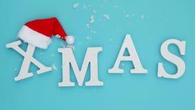 Smsa Xmas från vita bokstäver för volym i röd jultomtenhatt och fallande snö på blå bakgrund Glad jul f?r begrepp ?verkant arkivfilmer