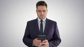 Smsande meddelande för allvarlig affärsman på hans telefon på lutningbakgrund arkivfilmer