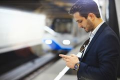 Smsande meddelande för attraktiv affärsman i mobiltelefon, medan vänta på drevet i tunnelbana royaltyfria foton