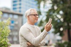 Smsande meddelande för hög man på smartphonen i stad royaltyfria bilder