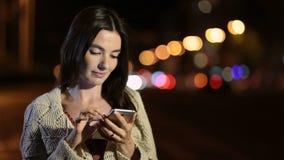 Smsande meddelande för lycklig flicka på telefonen i nattstad arkivfilmer
