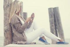 Smsande meddelande för skönhetung flicka på telefonen royaltyfria foton
