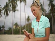Smsande meddelande för ung kvinna på smartphonen på stranden arkivfilmer