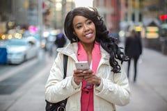 Smsande mobiltelefon för svart afrikansk amerikankvinna i stad Royaltyfri Foto