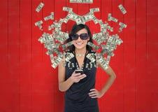 smsande pengar kvinna med rikt utseende med telefonen Pengar som kommer upp från telefonen arkivbild