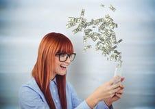 smsande pengar Ung kvinna för Hipster med telefonen Pengar som kommer upp från telefonen arkivbilder