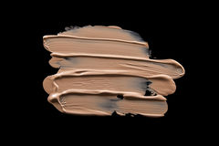 Smudged liquid foundation isolated on black. Smudged liquid make-up base isolated on a black background Royalty Free Stock Images