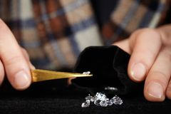 Smuggler of diamonds evaluating gems for dealing on velvet pad. Old style diamond smuggler watching quality of his goods Royalty Free Stock Photo