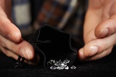 Smuggler of diamonds packing gems to velvet bag for dealing. Old style diamond smuggler watching quality of his goods Stock Photo