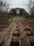 Smula bron med brutna träplankor och rostigt stål arkivbild