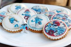 Smurf design gingerbread iced cookies. VARNA, BULGARIA DECEMBER 9, 2017: Pile of homemade Smurf design gingerbread iced cookies on a white plate with the focus Stock Photos