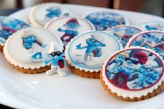 Smurf design gingerbread iced cookies. VARNA, BULGARIA DECEMBER 9, 2017: Pile of homemade Smurf design gingerbread iced cookies on a white plate with the focus Stock Images