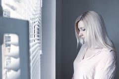 Smutna apatyczna osamotniona kobieta patrzeje przez okno lub poj?cia w domu hotelu, rozwodu, depresji i apatii, zdjęcie royalty free
