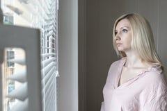 Smutna apatyczna osamotniona kobieta patrzeje przez okno lub poj?cia w domu hotelu, rozwodu, depresji i apatii, zdjęcie stock