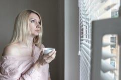 Smutna apatyczna osamotniona kobieta patrzeje przez okno lub poj?cia w domu z fili?anka kawy hotelu, rozwodu, depresji i apatii, zdjęcia royalty free