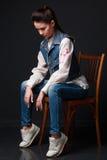 Smutna brunetki kobieta w cajgach przekazuje obsiadanie na krześle Obrazy Stock