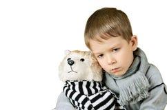 Smutna chłopiec ściska zabawkarskiego psa odizolowywającego na bielu fotografia royalty free