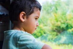 Smutna chłopiec jedzie pociąg i patrzeje out okno zdjęcia stock