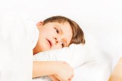 Smutna chłopiec kłaść w łóżku na białym tle Fotografia Royalty Free