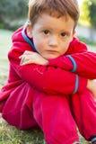 Smutna chłopiec outside na gazonie Fotografia Stock