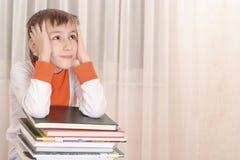 Smutna chłopiec robi pracie domowej na białym tle Fotografia Stock