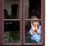 Smutna chłopiec, siedzi za okno zdjęcia royalty free