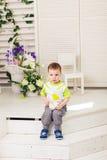 Smutna chłopiec z filiżanką w pokoju Zdjęcia Stock