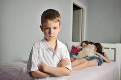 Smutna chłopiec z pobrużdżonymi brwiami w przedpolu w izbowym whith Fotografia Stock