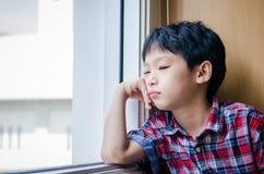 Smutna chłopiec patrzeje z okno Zdjęcia Royalty Free
