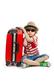 Smutna chłopiec siedzi przy czerwonym bagażnikiem Zdjęcia Royalty Free