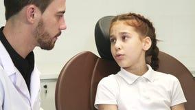 Smutna dziewczyna opisuje jej toothache lekarka zdjęcie wideo