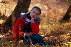 Smutna dziewczyna siedzi na jesieni trawie zdjęcia royalty free