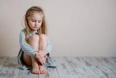 Smutna dziewczyna siedzi samotnie na podłoga zdjęcie royalty free