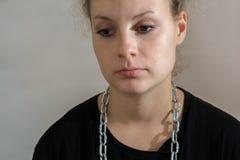 Smutna dziewczyna w czerni ubraniach z łańcuchem wokoło jej szyi fotografia stock