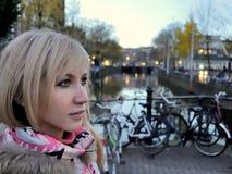 Smutna dziewczyna w różowej kurtce blisko kanału Amsterdam na błękitnym godzina wieczór wśród rowerów Fotografia Stock